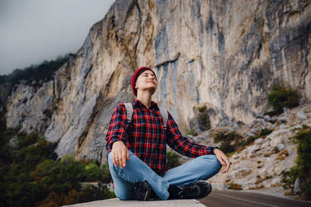 Asian hipster woman walking alone on a mountain highway on an autumn foggy day. The idea and concept of digital detox, solo travel and freedom