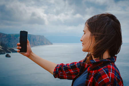 woman traveling with backpack tourist on seashore in summer. Enjoying Beautiful clouds sky among Mighty Cliffs Meeting Ocean. A woman takes a photo or video for social media