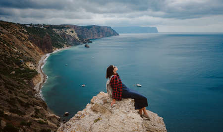 woman traveling with backpack tourist on seashore in summer. Enjoying Beautiful clouds sky among Mighty Cliffs Meeting Ocean. the idea and concept of freedom, vacation and discovery