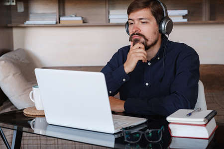 Happy male student online teacher wear headphone talk video calling, looking at laptop computer screen, do conference chat