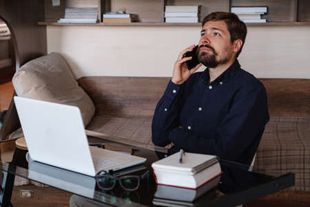 Handsome young man working on laptop. Businessman using phone. Freelance business work from home concept 免版税图像
