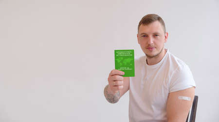 Adult man wearing t-shirt holding green International Certificate of Vaccination on white background. Traveling Immune passport, as proof vaccinated against Covid-19. 免版税图像