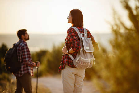 Portrait of happy young couple having fun on their hiking trip. Caucasian and asian hiker couple enjoying themselves on summer vacation. Young people hiking in nature.