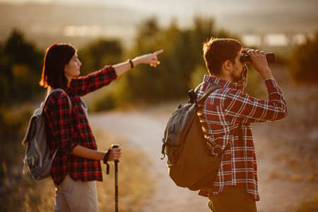 Portrait of happy young couple having fun on their hiking trip. Caucasian and asian hiker couple enjoying themselves on summer vacation. They are watching nature with binoculars.