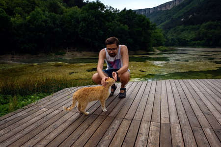A man is playing with a domestic red tabby cat. The cat rubs on the mans leg. after the rain