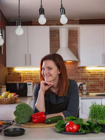 Healthy eating lifestyle concept portrait of beautiful young redhair woman preparing tasty food salat with broccoli, zucchini, red pepper, herbs on the table 免版税图像