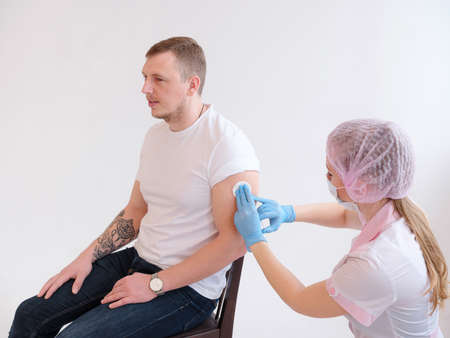 Female doctor holding syringe making vaccination injection dose in shoulder of male patient.