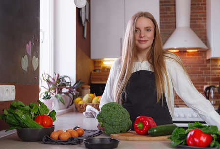 A young blonde happy lady standing in the kitchen while cooking healthy food. Healthy Lifestyle Concept. Cooking at home. broccoli, zucchini, red pepper, herbs on the table