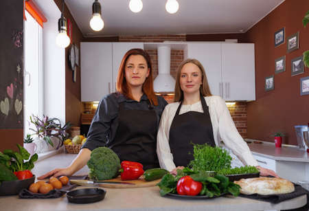 Young girlfriends in the kitchen cooking a vegetarian meal together. Cooking healthy and tasty Shakshuka. broccoli, zucchini, red pepper, herbs on the table