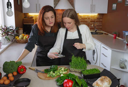 Young girlfriends in the kitchen cooking a vegetarian meal together. Cooking healthy and tasty Shakshuka. woman takes pictures and records video for culinary blog on smartphone
