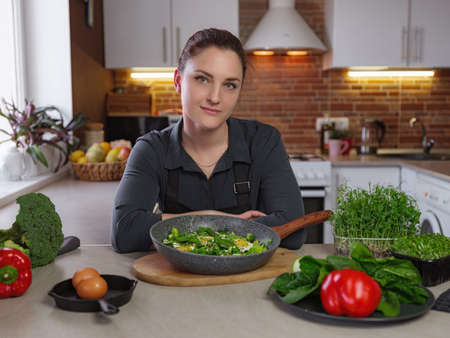 Healthy eating lifestyle concept portrait of beautiful young redhair woman preparing tasty food, green hot shakshuka cooked with love, broccoli, zucchini, red pepper, herbs on the table
