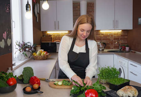 A young blonde happy lady standing in the kitchen while cooking healthy food. Healthy Lifestyle Concept. Cooking at home. cutting vegetables for cooking 免版税图像