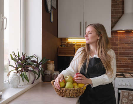 A young blonde happy lady standing in the kitchen while cooking healthy food. Healthy Lifestyle Concept. Cooking at home.