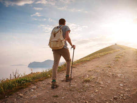 Young man travels alone walking on trail and enjoying on view of mountains and sea landscape at sunset, the lifestyle concept of traveling outdoors. Standard-Bild
