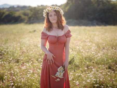 red-haired woman wearing dress and chamomile wreath on field on summer evening. concept of digital detox, digital cleanse, reconnecting with nature, calmness and silence