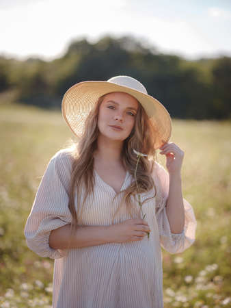 Beautiful pregnant woman in dress and hat relaxing outside in chamomile field. Right choice for your baby digital detox and reconnecting with nature.