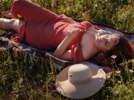 red-haired woman wearing dress and hat on summer evening field of daisies lies and dreams. concept of digital detox, digital cleanse, reconnecting with nature. Stock Photo