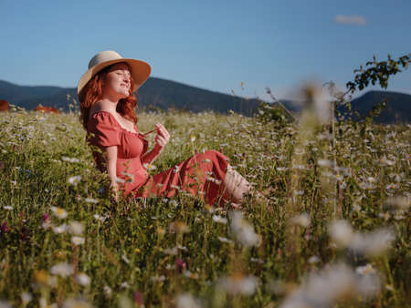 red-haired woman wearing dress and hat on summer evening field of daisies reading a book while sitting on a blanket. concept of digital detox, digital cleanse, reconnecting with nature.