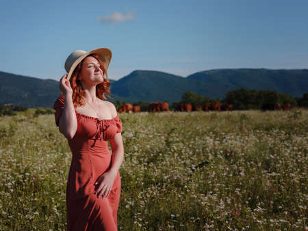 red-haired woman wearing dress and hat on summer evening field of daisies. concept of digital detox, digital cleanse, reconnecting with nature.
