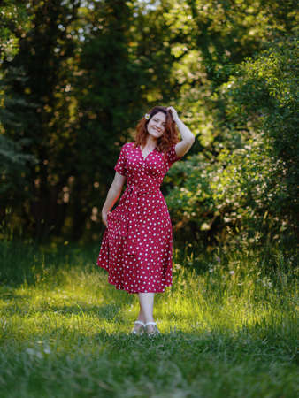 Ginger Woman wearing orange dress in green forest enjoys the silence and beauty of nature. idea and concept of wellness, celebration of lifes little moments Stock Photo