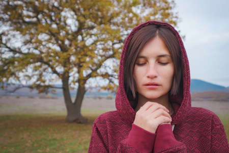 Portrait of a young asian woman in hoodie in the autumn nature. Outdoor atmospheric lifestyle portrait. Season and people Stock Photo