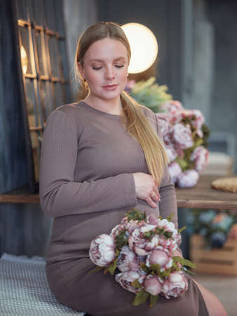 Beautiful pregnant blonde woman resting at home, boho or rustic room. Caring for women's health. pregnancy, vacation, people and expectation concept Stock Photo