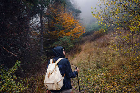 young man traveler in autumn misty nature. rear view. concept active healthy lifestyle, adventure and travel vacation
