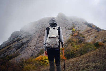 Asian travel woman stands by the mountain. Cold weather, fog on the hills. Autumn hike. The beginning of the autumn season. Beautiful foggy weather Stock Photo