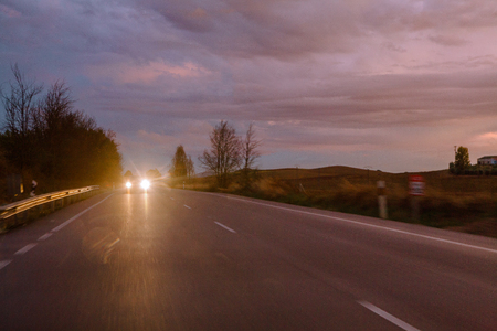 Vehicle with bright headlamps riding along asphalt road in amazing countryside in cloudy evening