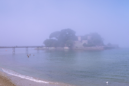 Beautiful view of bridge to amazing island fortress on foggy day near sea Фото со стока