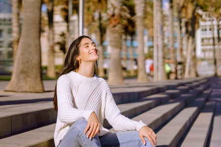 Side view portrait of a young woman relaxing breathing fresh air Stockfoto