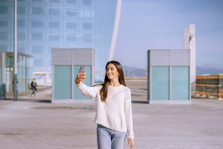 happy young woman walking and taking a selfie in the city - image