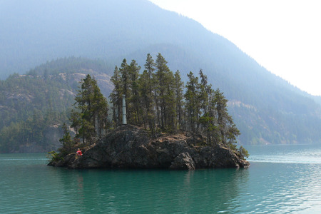 lake diablo: olated Island with a little Light House within Diablo Lake in Washington