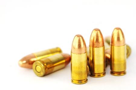 Live 9mm pistol round against white
