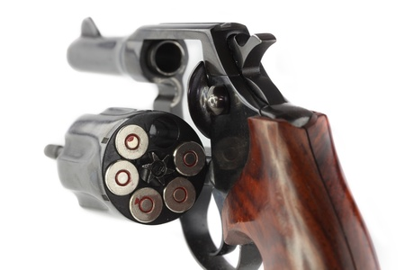 Close up of handgun revolver with bullets on white background