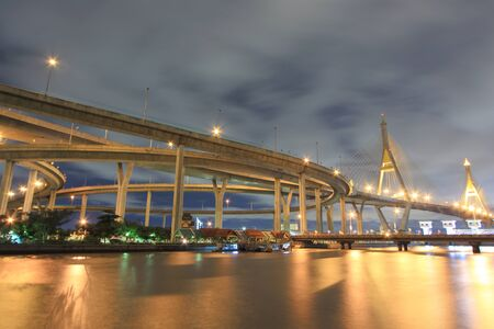 Curve of suspension bridge at riverside in twilight scene Bangkok, Thailand