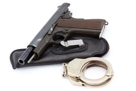 restraining device: Handgun automatic and handcuff on white background