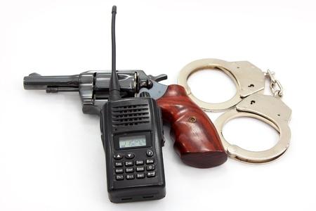 wrist cuffs: Handgun revolver and Handcuff with Police Radio communication on white background Stock Photo