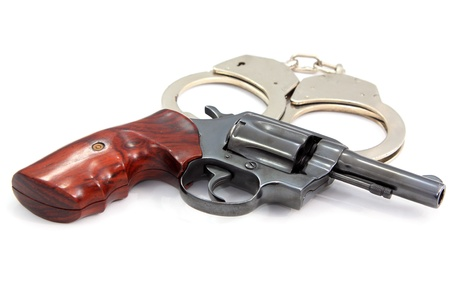 Handgun revolver and handcuff on white background Stock Photo - 16946216