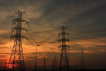 High voltage power pylons in sunset scene twilight photo