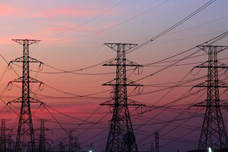 Altas torres de tensi?n de alimentaci?n en la puesta del sol escena crepuscular
