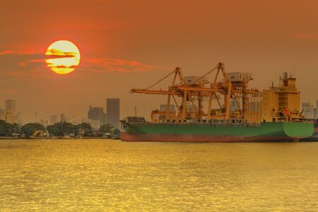 Container Cargo freight ship with working crane bridge in shipyard at sunset
