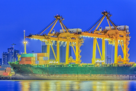 Container Cargo freight ship with working crane bridge in shipyard at twilight photo
