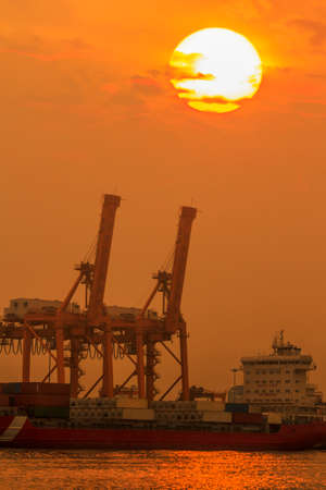 Container Cargo freight ship with working crane bridge in shipyard at sunset photo