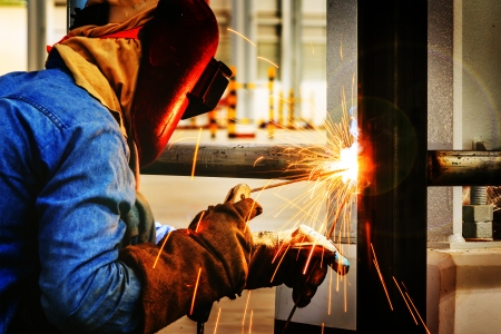Welder working a welding metal with protective mask and sparks Imagens