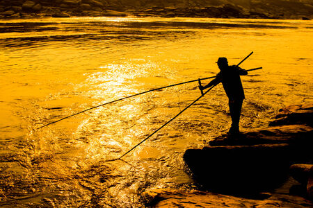Fishermen fishing at river in sunset,Thailand photo