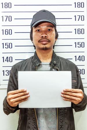 Man holding a white paper taking criminal mug shot  photo