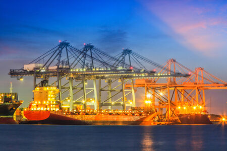 Industrial Container Cargo freight ship with working at twilight photo
