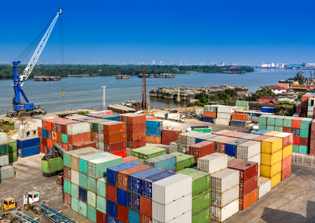 dockyard: Industrial Container Cargo in harbor beside river Editorial