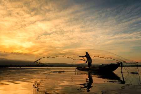 Fishermen on boat fishing at lake in Thailand photo